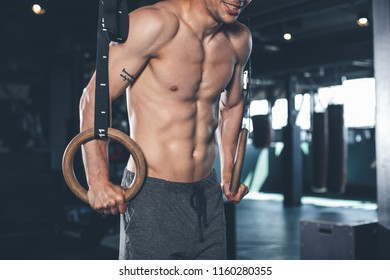 Cheerful shirtless guy is pulling up with equipment. He is hanging while grabbing rings and balancing on them. Athlete is enjoying training in gym