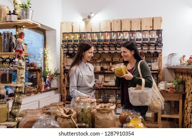 Cheerful shop assistant helping customer in packaging free shop. Zero waste shopping - woman buying fresh spices and herbs at package free grocery store.