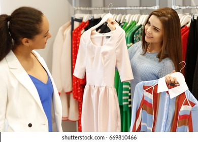 Cheerful shop assistant helping her female customer choosing dresses working at the store profession occupation friendly helpful advise people lifestyle consumerism purchasing positivity retail sales