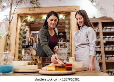 Cheerful shopkeeper helping customer in packaging free shop. Zero waste shopping - woman choosing natural homemade soap at package free store.