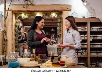 Cheerful shopkeeper helping customer in packaging free shop. Zero waste shopping - woman buying natural homemade soap at package free store.