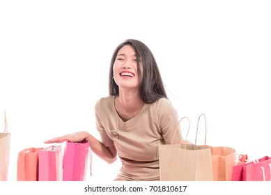 Cheerful shopping woman of Asian descent holding bags. Shopping smart business woman happy smiling holding colorful shopping bags isolated on white .   young Asian female model