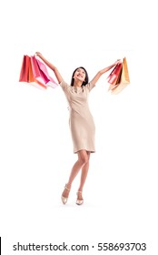 Cheerful shopping woman of Asian holding bags. Shopping smart business woman happy smiling holding colorful shopping bags isolated on white . Fresh young Asian female model
