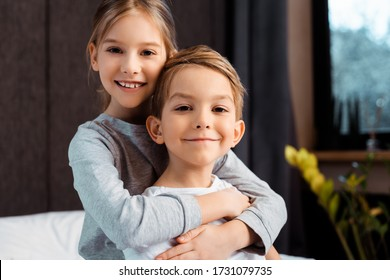cheerful sister hugging happy brother at home
