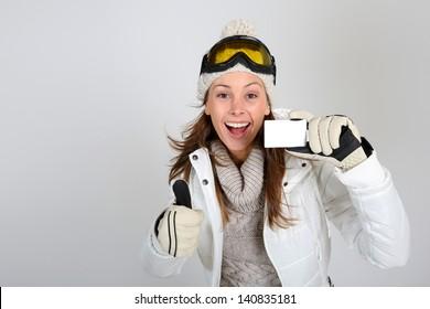 Cheerful skier woman showing ski pass
