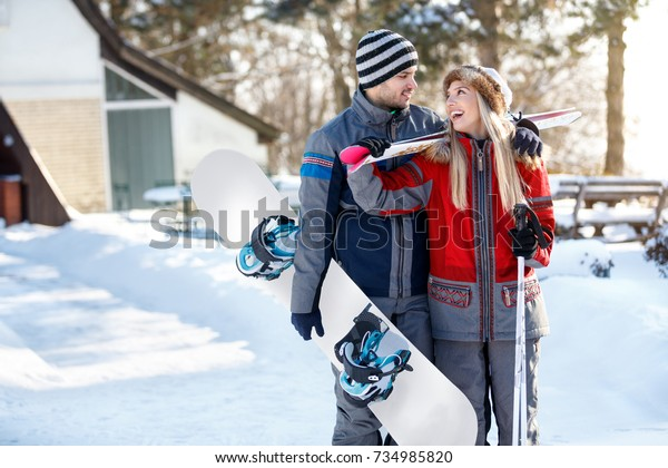 Cheerful skiers couple in love with skis and ski board going to ski terrain