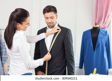 Cheerful skilled clothes designer is serving her customer. She is standing near a man in suit and measuring the size of his collar. She is holding a tape-line with joy. They are smiling