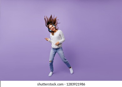 Cheerful, slightly crazy girl playing imaginary guitar, listening to big headphones in big headphones. Studio portrait of musician with dark hair flying
