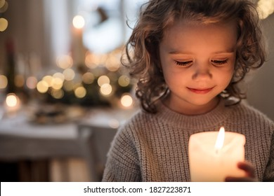 Cheerful small girl indoors at home at Christmas, holding candle.
