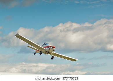 Cheerful  small plane in the blue cloudy sky
