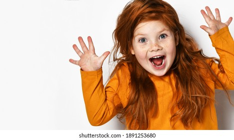 Cheerful small red haired girl with freckles in yellow comfortable longsleeve standing showing fingers and feeling excited over white background. Happy childhood, stylish look concept