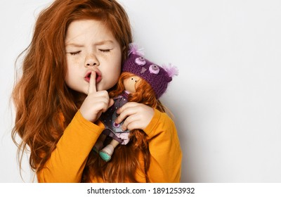 Cheerful small red haired girl in yellow comfortable longsleeve standing holding toy doll in hands and showing silence sign with finger over white background, copy space. Happy childhood, stylish look
