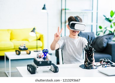 Cheerful smart boy wearing VR glasses while using them to test his humanoid robotic hand