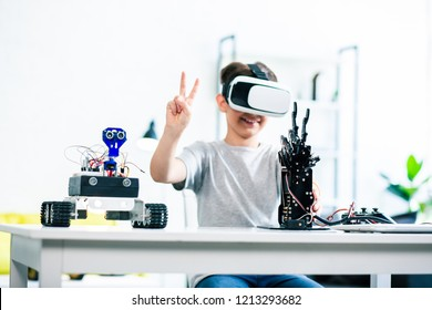 Cheerful smart little boy sitting at the table and testing his robotic creating by means of VR technologies