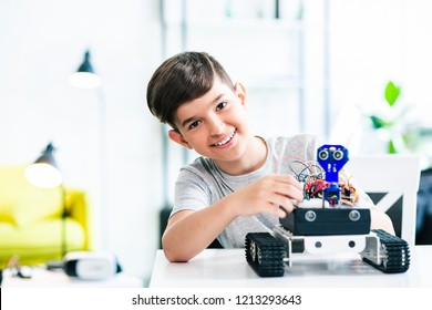 Cheerful smart schoolboy sitting at the table and constructing a robotic device at home