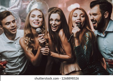 Cheerful. Smile. Smiling Girl. Singing Songs. Beautiful Girls. Friends at Karaoke Club. Karaoke Club. Celebration. Waiting Men. Young People. Party Maker. Girls Sing. Trendy Nightclub. Have Fun.