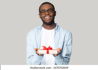 Cheerful smiling african american millennial guy in eyewear holding wrapped present box head shot portrait. Happy black young man congratulating, giving birthday gift, isolated on grey background.