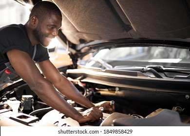 cheerful smiling afro man enjoy repairing car's hood, check the details,fixes machine problems