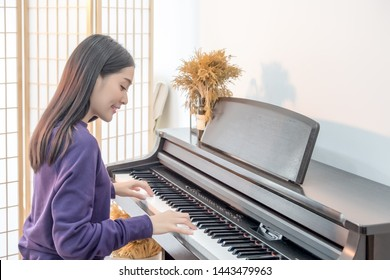 Cheerful Smiling asian young girl playing piano in sost light. Beautiful,happy, joyful, relaxing woman practising piano cheerfully.