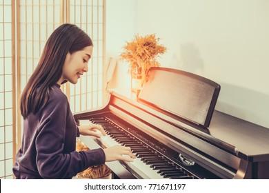 Cheerful Smiling asian young girl playing piano in sost light. Beautiful,happy,  joyful, relaxing woman practising piano cheerfully.