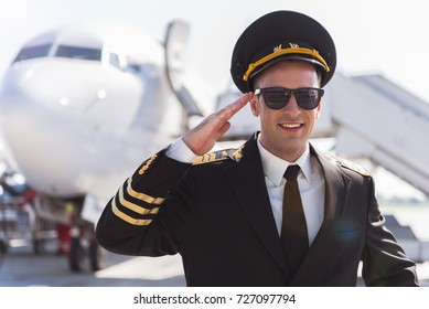 Cheerful smiling aviator standing outside