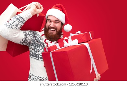 Cheerful and smiling Bearded guy wearing stylish winter clothes brings gifts over red background