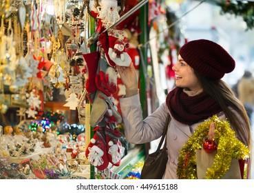 Cheerful smiling beautiful girl choosing Christmas decoration at market