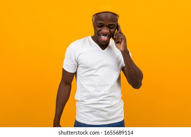 Cheerful smiling black man American in a white T-shirt talking on the phone on an orange studio background with copy space
