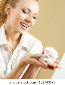 Cheerful smiling blond woman eating cake, at home