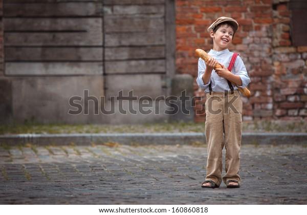 屋外でバゲットを持つ陽気な笑顔の少年