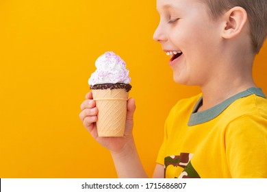 Cheerful smiling boy holding ice cream on yellow background. Concept of joy and happiness