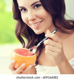 Cheerful smiling brunette woman eating grapefruit at home. Healthy eating, beauty and dieting concept.