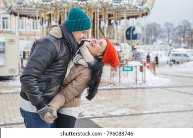 Cheerful smiling caucasian couple of man and woman having fun on european street walk. Casual outfit: jeans, jackets and hats. Winter cold weather with snow. Decorated Christmas tree on a background