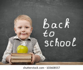 Cheerful smiling child with a book and apples stands at the blackboard. Looking at camera. School concept