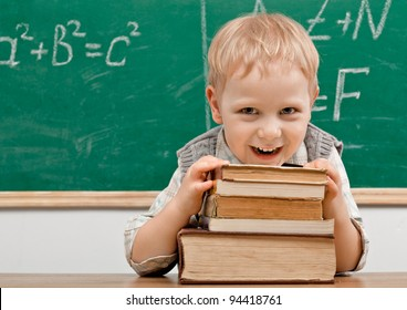 Cheerful smiling   child resting on a stack of books in a classroom. Looking at camera. School concept