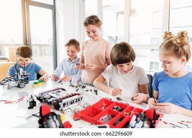 Cheerful smiling children constructing lego