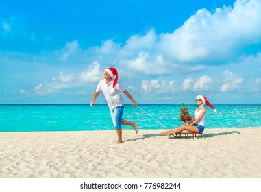 Cheerful smiling couple in red Santa hats walking at tropical ocean sandy beach with sleds and decorated fir-tree. Happy New Year and Merry Christmas vacation in hot countries concept
