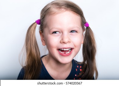 Cheerful smiling cute child with teeth dropped out - preschooler girl with open mouth without milk tooth
