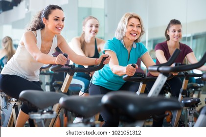 Cheerful smiling different age females cycling on exercise bikes at fitness club