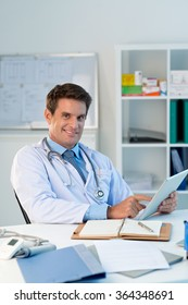 Cheerful smiling doctor with a digital tablet sitting at his table