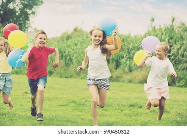 cheerful smiling elementary school age boy and girls holding air balloons and running in summer park. Selective focus