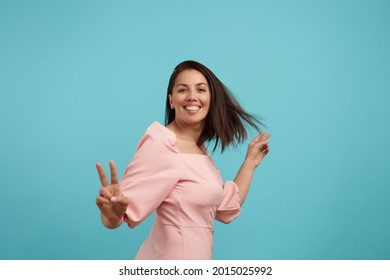 Cheerful smiling european woman with dark hair in pink dress dances, smiles broadly, feels lively and energetic, makes victory gesture, spends free time on disco party, moves against blue background