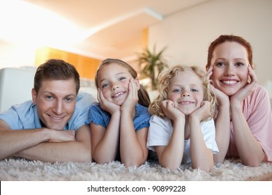 Cheerful smiling family on the carpet