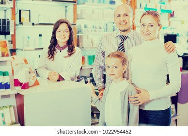 Cheerful smiling family of three happy persons getting help of a pharmacist in the pharmacy