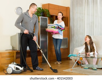 Cheerful smiling family of three tidying up a room all together. Focus on man