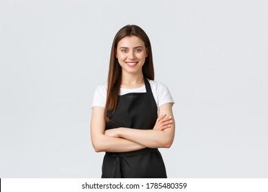 Fröhlich lächelnde weibliche Barista in schwarzer Schürze Kreuz-Brust, bereit und zuversichtlich. Junge Mädchenangestellte eröffnen Café, Grußkunde. Verkaufsabteilung