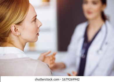 Cheerful smiling female doctor and patient woman discussing current health examination while sitting in sunny clinic. Medicine concept