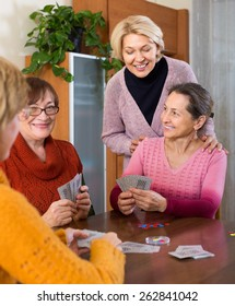 Cheerful smiling female pensioners playing cards at home