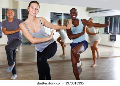 Cheerful smiling  friendly  people practicing vigorous lindy hop movements in dance class