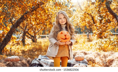 Cheerful and smiling ginger young adult mother holding hands with little daughter, looking at carved pumpkin with smoke and laughing. Woman making decoration for halloween with her charming child